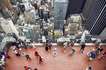 Tourist people taking pictures from rooftop on Manhattan skyscraper