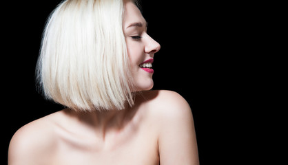 Woman with short hair shiny and bare shoulders with a smile, looking away on a black background