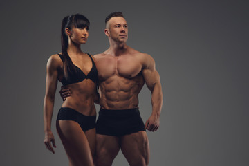 Fitness couple isolated on a grey background.