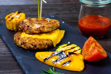 two fried cutlets next to peppers and tomatoes