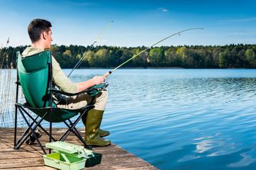 Man fishing at lake sitting on jetty