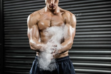Shirtless man clapping hands with talc