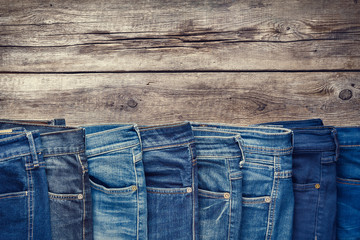 Fashion different jeans on wooden background. Retro toned.