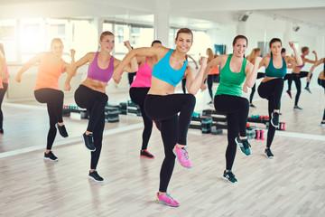 Grupa dysponowane młode kobiety robi ćwiczeniu wpólnie