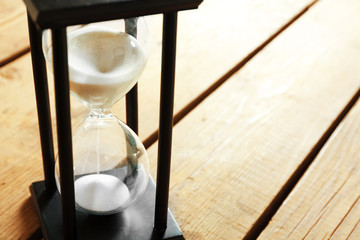 Black hourglass on wooden background, close up
