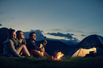Trzech przyjaciół obozuje z ogniem na górze o zachodzie słońca
