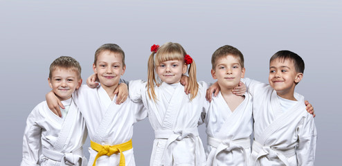 On a gray background little athletes in karategi