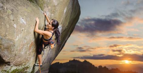Młody atrakcyjny żeński arywista wspina się wymagającą trasę na stromej skały ścianie przeciw scenicznemu zmierzchu tłu. Czas letni Sprzęt wspinaczkowy