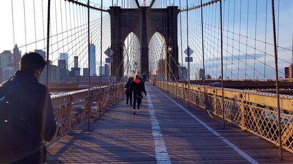 People walking on the Brooklyn Bridge towards Manhattan in the evening, New York.