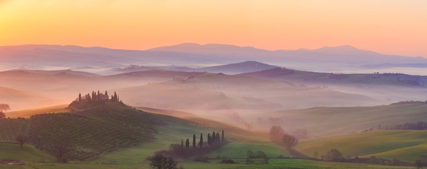 Misty sunrise in the Val d'Orcia, or Valdorcia, a region of Tuscany, central Italy, which extends from the hills south of Siena to Monte Amiata.