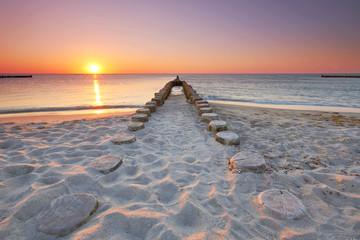 lange hölzerne Buhnen am Strand, Sonnenuntergang am Meer