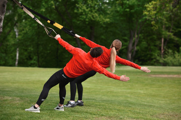 Portrait of sport or fitness man and woman training in park. Back sides of couple during exercising in green park or forest.