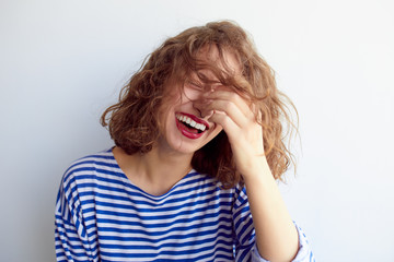 Laughing woman with curly hair on white wall