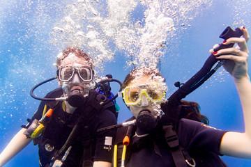 Mann und Frau beim Tauchen im tropischen Meer steigen wieder auf nach Tauchgang