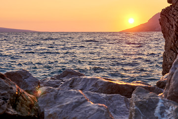 Rock island at sunset in small mediterranean town Brela , Croati