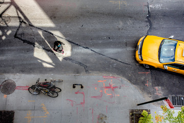 View of from above of urban street in New York City Manhattan with yellow taxi cab and pedestrian