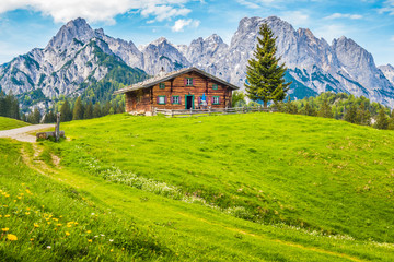 Idyllic scenery in the Alps with mountain chalet and green meadows