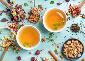 Dwie szklanki zdrowej herbaty ziołowej z miętą, cynamonem, suszoną różą i rumiankiem w łyżkach na niebieskim tle