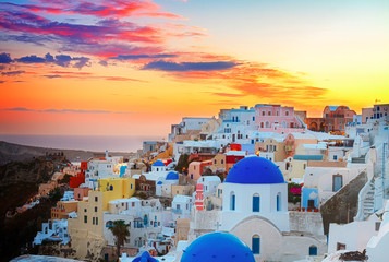 cityscape of Oia, traditional greek village of Santorini,  with blue domes of churches at sunset, Greece, toned