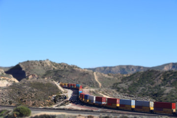Train going through mountains, tilt shifted image