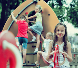 Smiling girl sitting on swing on children's playground