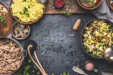 Delicious dish with  stewed chopped cabbage and mushrooms, yellow rice and mincemeat on dark background , top view. Rustic food cooking