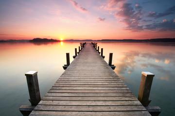 langer Holzsteg am Seeufer zum Sonnenaufgang im Sommer