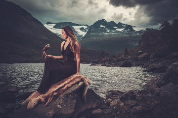 Nordic goddess in ritual garment with hawk near wild mountain lake in Innerdalen valley.