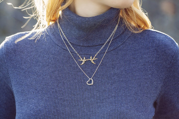 woman wearing a jewelry on her turtleneck