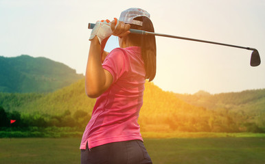 Young women player golf swing shot on course in morning sunrise