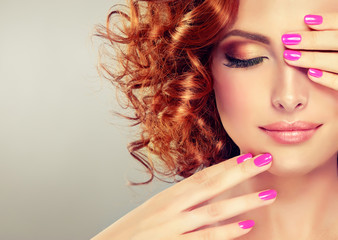 Beautiful model girl with curly red hair . Magenta color  manicure on nails .