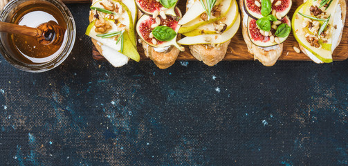 Crostini with pear, ricotta cheese, honey, figs, nuts and fresh herbs. Breakfast toasts or snack sandwiches on rustic wooden board over dark blue grunge plywood background. Top view, copy space