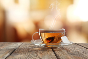 Glass cup of tea on wooden table and blurred color background