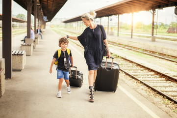 Cute little boy and mother on a railway station