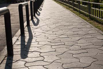 Streszczenie światła i cienia na drodze z ogrodzenia