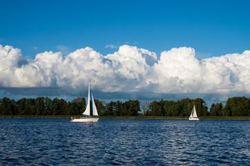 Dwa jachty żaglowe żeglujące po jeziorze, w tle rozbudowujące się chmury Cumulus