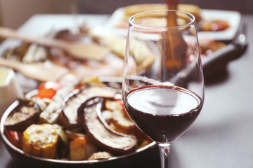 Glass of wine and grilled vegetables on served table