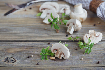 Fresh mushrooms and basil on rustic wooden background.