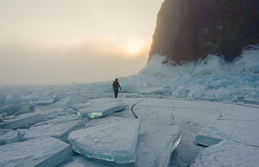 man walking in the fog on the ice of lake Baikal