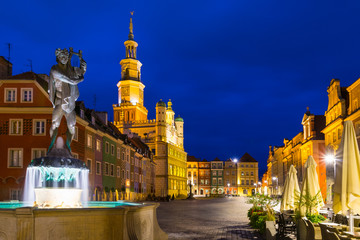 Night photo of Poznan Old Town with Saint John of Nepomuk statue and numerous of illuminated townhouses.