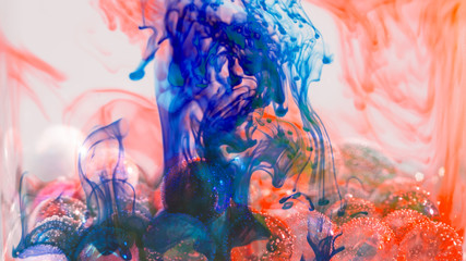 Kształty tuszu w szklanym wazonie nad szklanymi kulkami z bąbelkami