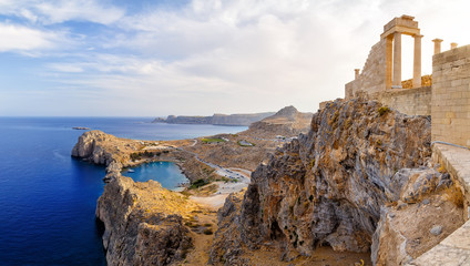 Greece. Rhodes. Acropolis of Lindos. Doric columns  the ancient Temple  Athena Lindia the IV century BC and the bay  St. Paul