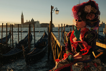 A soft picture of a lady in carnival costume holding her mask wi
