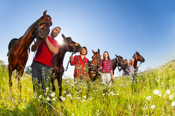 Five happy equestrians walking with their horses