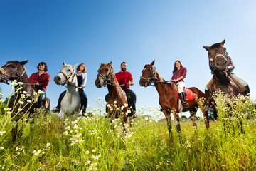 Portrait of happy equestrians riding their horses