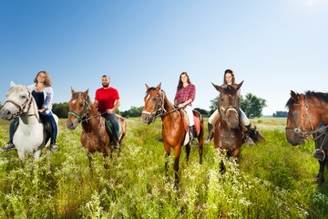 Happy equestrians riding horses in summer field