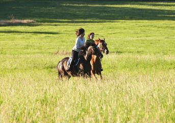 Two Women Horseback Riding in a Landscape