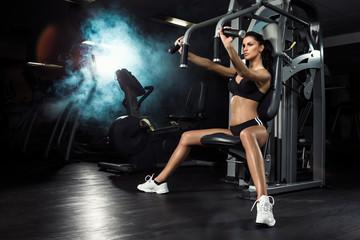 Fitness, trening, młoda piękna dziewczyna trenuje na siłowni