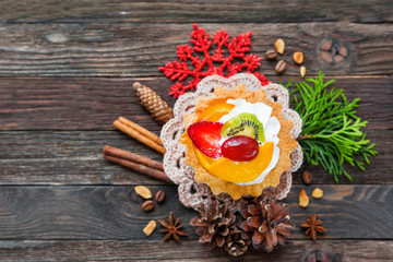 Christmas and New Year 2017 background with fruit tart and decorations - snowflake, crochet napkin, pine cones. Place for text.