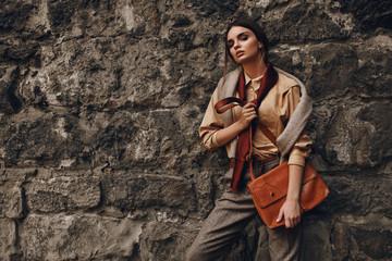Beautiful Fashionable Woman In Fashion Clothing Posing Near Wall
